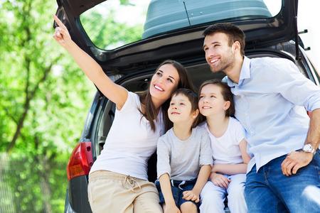 Photo pour Happy family of four sitting in car trunk  - image libre de droit