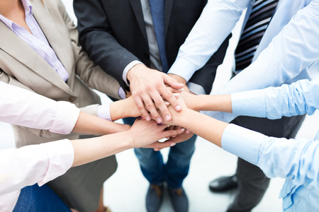 Photo pour Business people joining hands in circle - image libre de droit