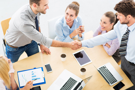 Photo pour Business people shaking hands across table - image libre de droit