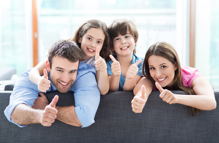 Foto de Family at home with thumbs up - Imagen libre de derechos