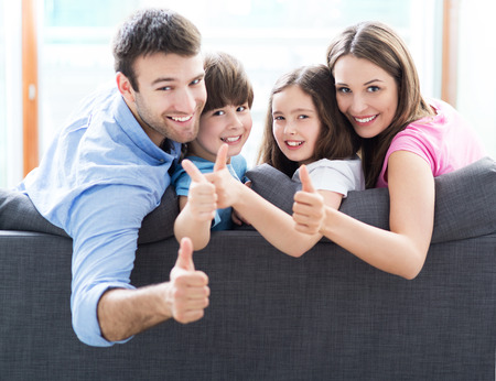 Photo pour Family at home with thumbs up - image libre de droit