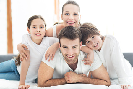 Foto de Family of four lying on bed - Imagen libre de derechos