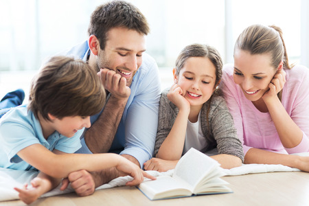 Photo for Happy family reading book together - Royalty Free Image