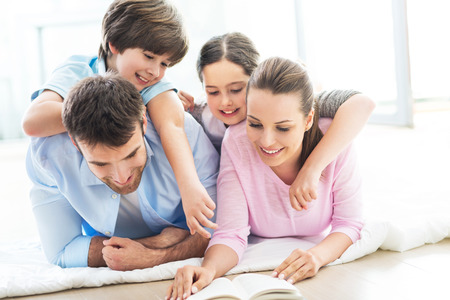 Photo pour Happy family reading book together - image libre de droit