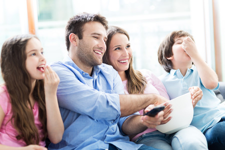 Photo pour Family watching TV and eating popcorn - image libre de droit