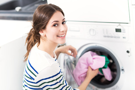 Foto per Woman loading washing machine - Immagine Royalty Free
