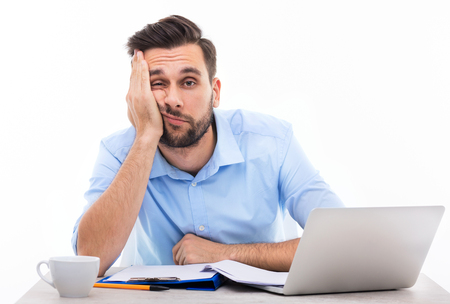 Photo pour Bored young man at the desk - image libre de droit