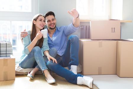 Foto de Couple on floor next to moving boxes - Imagen libre de derechos