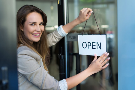 Photo for Woman hanging open sign on door - Royalty Free Image