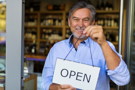 Photo pour Wine shop owner holding open sign - image libre de droit