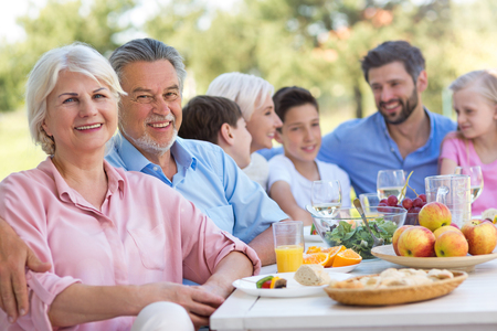 Photo pour Extended family eating outdoors - image libre de droit