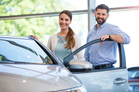 Photo for Young couple in the showroom, choosing a car - Royalty Free Image