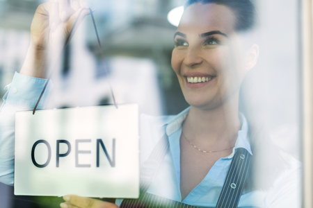 Photo for Woman holding open sign in cafe - Royalty Free Image