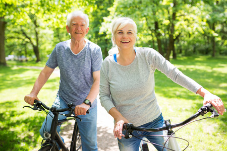 Photo for Senior Couple Riding Bikes In Park - Royalty Free Image