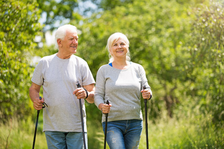 Photo for Senior couple Nordic walking in park - Royalty Free Image