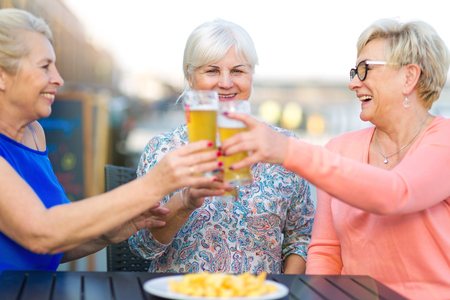 Photo for Smiling senior women having a beer in a pub outdoor - Royalty Free Image