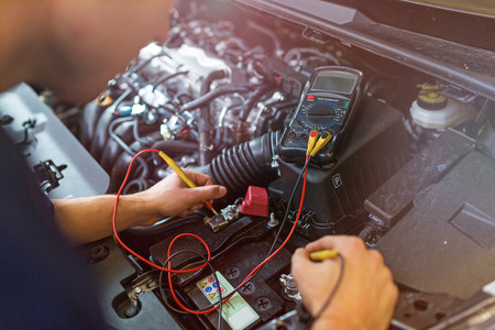 Foto de Auto mechanic checking car battery voltage - Imagen libre de derechos