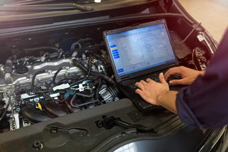 Foto de Mechanic Using Laptop While Examining Car Engine - Imagen libre de derechos