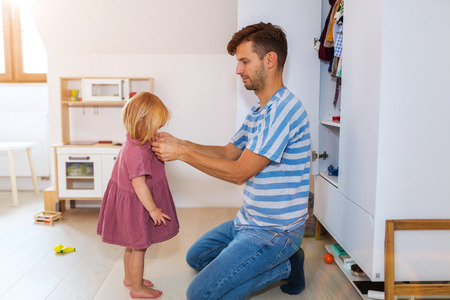 Photo pour Dad is helping toddler daughter to get dressed - image libre de droit