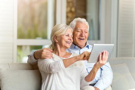 Foto de Senior couple using digital tablet at home - Imagen libre de derechos