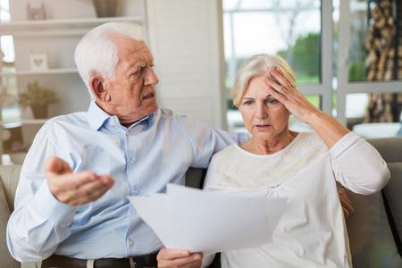 Foto de Senior couple looking through bills - Imagen libre de derechos