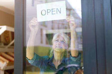 Foto de Senior woman holding an open sign in organic produce shop - Imagen libre de derechos