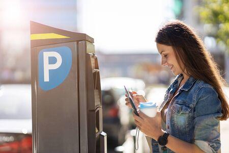 Foto de Young Woman Using Parking Machine - Imagen libre de derechos