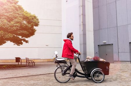 Photo pour Young man going back from shopping with a cargo bike - image libre de droit