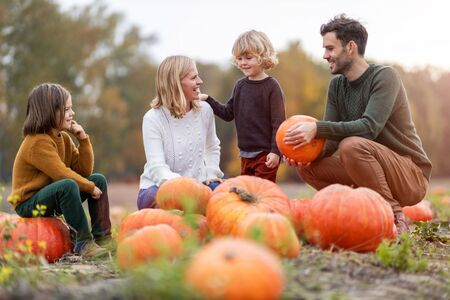 Photo pour Happy young family in pumpkin patch field - image libre de droit