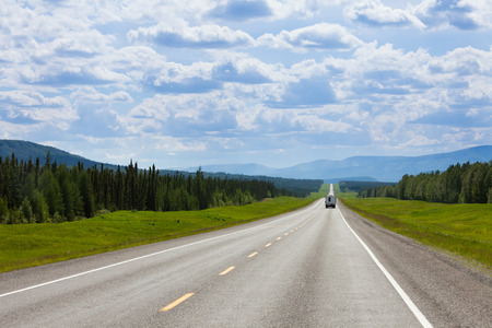 Photo for Recreational Vehicle RV southbound on empty road of Alaska Highway, Alcan, in boreal forest taiga landscape south of Fort Nelson, British Columbia, Canada - Royalty Free Image