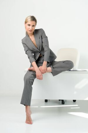 Young beautiful businesswoman is sitting on the table in the office. Break relaxing time