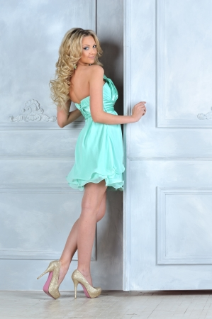 Photo for Beautiful blonde in blue short dress at the opening door. - Royalty Free Image