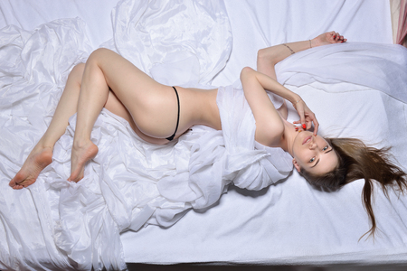 Foto de Beautiful womanin panties laying on the bed. View from above, high angle - Imagen libre de derechos