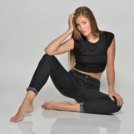 Foto de Portrait of the sexy beautiful woman in black posing in studio with grey background. She is sitting on the floor. - Imagen libre de derechos