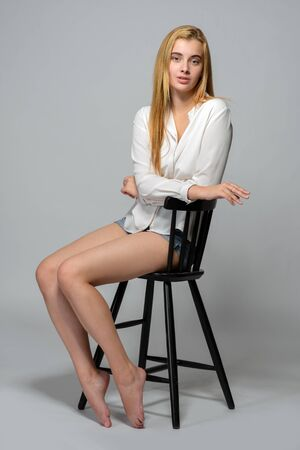 Foto de beautiful barefoot woman in jeans shorts and white shirt. She is sitting on high chair in studio with gray background. - Imagen libre de derechos