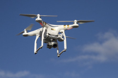 Foto de small unmanned helicopter with a camera flying in the blue sky - Imagen libre de derechos