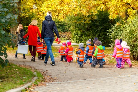 Foto de Tallinn, Estonia - October 19, 2015: A kindergarten teacher with small children dressed in reflective safety vests for a walk in the park in Tallinn. - Imagen libre de derechos