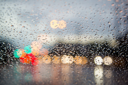 blurred image of traffic view through a car windscreen covered in rain