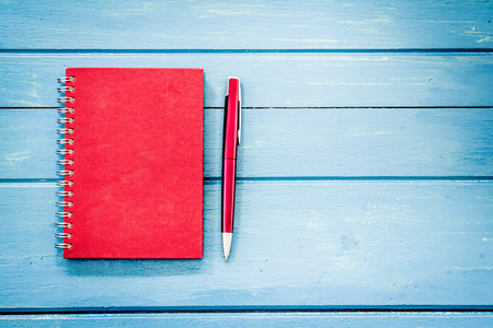 Photo for Red notebook with pen on blue wooden table - Royalty Free Image