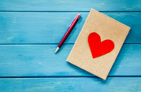 Foto de love heart on notebook with pen on blue wooden table - Imagen libre de derechos