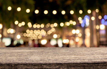 Photo pour wooden table with abstract bokeh in night shopping mall  background - image libre de droit