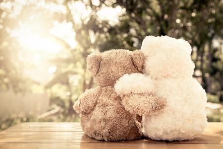 Foto de Couple teddy bears in love's embrace sitting on wooden table in the garden with sunlight,vintage color filter - Imagen libre de derechos