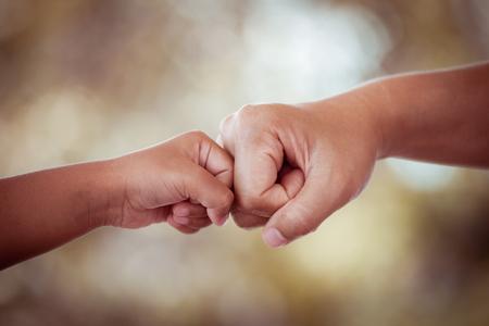 Foto de mother and kid daughter are fist bumping in vintage color tone - Imagen libre de derechos