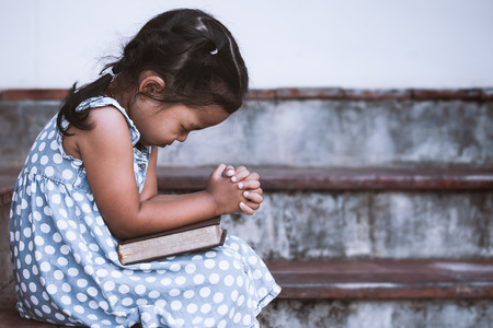 Foto de Cute asian little girl closed her eyes and  folded her hand in prayer on a Holy Bible for faith concept in vintage color tone - Imagen libre de derechos
