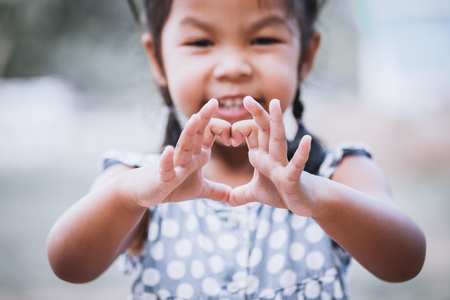 Foto de Asian little girl making heart shape with hands in vintage color tone - Imagen libre de derechos