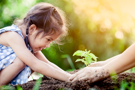 Photo pour Asian little girl and parent planting young tree on black soil together as save world concept in vintage color tone - image libre de droit