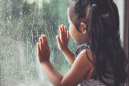 Foto de Sad asian little girl looking outside through the window in the rainy day in vintage color tone - Imagen libre de derechos