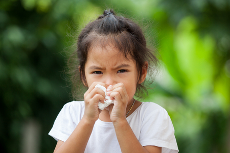 Photo pour Sick little asian girl wiping or cleaning nose with tissue on her hand - image libre de droit