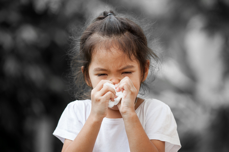 Photo pour Sick little asian girl wiping or cleaning nose with tissue on her hand on black and white background - image libre de droit