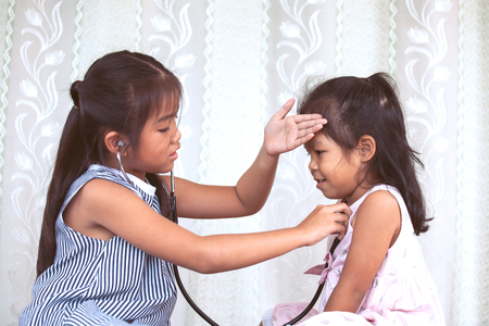 Foto de Two cute asian little child girls playing doctor and patient together in vintage color tone - Imagen libre de derechos